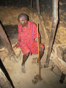 Inside the Masai hut, our host sits on his bed.