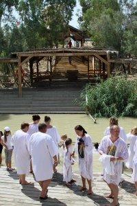 The River Jordan looking over to the Jordanian side with people getting baptized.