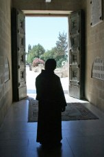 A monk meditates on the view outside the Church of Transfiguration.